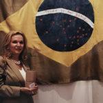 Ana Maria Vieira Santos em frente à bandeira bordada com fios de seda e tingida com corantes do Pau-Brasil